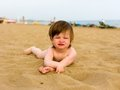 Toddler girl laying on the sand beach Royalty Free Stock Image