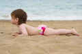 Toddler girl laying on the sand beach Stock Photography