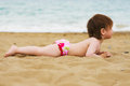 Toddler girl laying on the sand beach Stock Photos