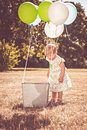 Toddler girl near basket with balloons outdoors party looking into Royalty Free Stock Photography