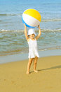 Toddler girl playing with her inflatable ball at beach Royalty Free Stock Image