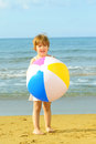 Toddler girl playing with her inflatable ball at beach Royalty Free Stock Photos