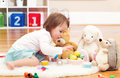 Toddler girl playing with her stuffed animals Royalty Free Stock Photo