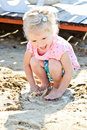 Toddler girl and puddle in sand soft selective focus Royalty Free Stock Images