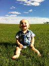 Toddler on grassy hill clear day Royalty Free Stock Image
