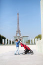 Toddler with his pram pushing at tour eiffel paris Royalty Free Stock Photo