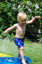 Toddler jumping over water-slide Royalty Free Stock Photography