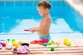 Toddler kid girl playing food toys in swimming pool Royalty Free Stock Photo