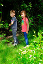 Toddler kids exploring two little walking together in the woods shallow depth of field Stock Photos