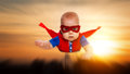 Toddler little baby superman superhero with a red cape flying th Royalty Free Stock Photo