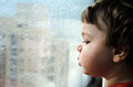 Toddler looking out of window on rainy day Stock Image