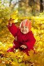 Toddler with maple leaves in autumn