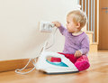 Toddler playing with electric iron