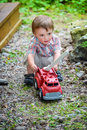 Toddler Playing with a Toy Fire Truck Outside - Series 1 Royalty Free Stock Photo