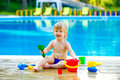 Toddler by the pool with toy bucket set Royalty Free Stock Photo