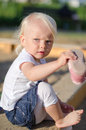 Toddler put on her shoes near sandbox Stock Photos