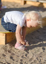 Toddler put on her shoes near sandbox Royalty Free Stock Photo