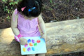 Toddler reading a book outdoors. Royalty Free Stock Photo