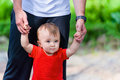Toddler in red shirt walking assisted by his father Royalty Free Stock Image