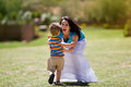 Toddler running towards he s mother an outdoor photo of a beautiful with her arms open cheerfully Stock Photography