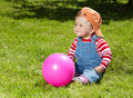 Toddler sit with ball in the garden Stock Image