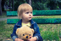 Toddler sitting on the bench in the park Royalty Free Stock Photo
