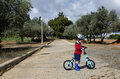 Toddler sitting on his balance bicycle cute boy mud Stock Photography