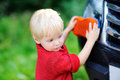Toddler son washing fathers's car Royalty Free Stock Photo