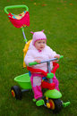 Toddler on a tricycle mother and baby taking and afternoon walk in the park Stock Image