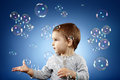 Toddler trying to catch bubbles little boy soap studio shot over blue background Royalty Free Stock Images