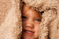Toddler under covers smiling hiding in fur blanket Royalty Free Stock Photo