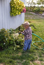 Toddler watering the garden Royalty Free Stock Image