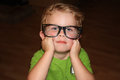 Toddler wearing glasses cute little boy oversized black rimmed in a contemplative pose Stock Photos