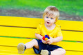 Toddler on the yellow bench cute sitting bright in park Royalty Free Stock Photography