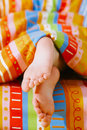 Toddlers girl feet in a bed under the morning sun Stock Photography