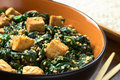 Tofu spinach and sesame stir fry fried with garlic ginger cooked rice in the back selective focus focus on the front of the Stock Photo