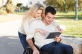 We together young disabled men and his girlfriend with digital tablet Royalty Free Stock Photography