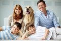 Togetherness portrait of happy family with fluffy labrador having rest at home Royalty Free Stock Photos