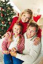 Togetherness portrait of happy family of three looking at camera on christmas day Stock Photography
