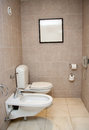 Toilet room with phone white sink and bidet Royalty Free Stock Photography