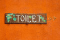 Toilet wood label on the orange wall. Royalty Free Stock Photography