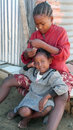 Toliara madagascar a girl combs to another while they are sitting in a street Stock Photo
