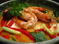 Tom yum kung nam khon creamy thai soup with prawns and mushroom garnished with coriander leaves and served with lime wedges Royalty Free Stock Photo