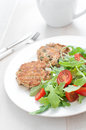 Tomato and arugula salad with fish patties tomatoes Royalty Free Stock Photo