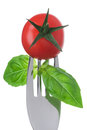Tomato and basil on a fork on white Royalty Free Stock Photography