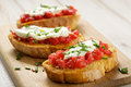 Tomato bruschetta with mozzarella cheese and fresh chive thyme on wooden board delicious vegetarian appetizer Stock Photos