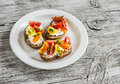 Tomato and cheese bruschetta on a white plate on rustic light wooden board. Royalty Free Stock Photo