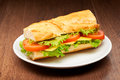 Tomato, cheese and salad sandwich from fresh baguette on white ceramic plate on dark wooden table Royalty Free Stock Photo