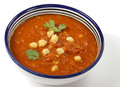 Tomato and chickpea soup spicy in a traditional tunisian bowl with a spoon garnished with parsley Royalty Free Stock Photo