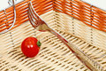 Tomato and fork in a basket of multicolored straws light background Stock Photo